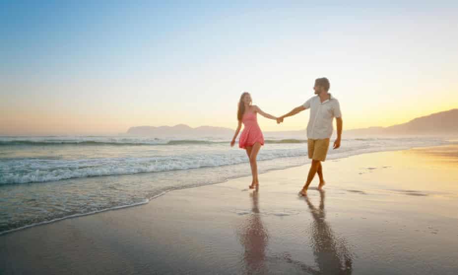 A couple walks along the beach.