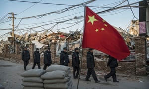 Chinese police walk in a line passed buildings demolished by authorities in an area that used to have migrant housing and factories. Rare protests have broken out in Beijing over the evictions.