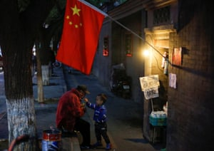 A man plays with a child underneath a Chinese national flag in a hutong alley in the old part of Beijing as the capital prepares for the Congress