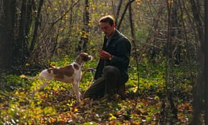 A man kneeling down in the forest holding something, a dog sniffing his hand
