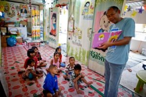 Thai teacher Pairote Chantawong reads a book to students, sons and daughters of Cambodian migrant workers