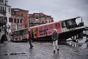 People walk past a stranded taxi boat on Riva degli Schiavoni