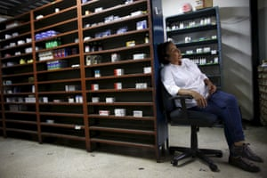 A worker awaits customers at a pharmacy in Caracas