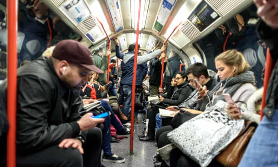 People on a London Underground tube train sitting and standing in the carriage.