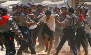 Police beat a student protester during the student march on Yangon in March 2015.
