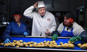 Boris Johnson with quality control staff during an election campaign visit to a crisp factory in County Armagh, Northern Ireland.