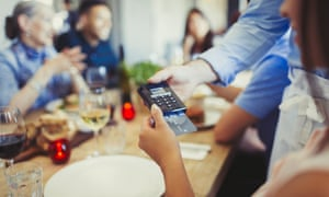Woman paying waiter with credit card