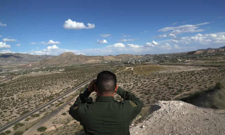 An agent scans the US-Mexico border at Sunland Park, New Mexico ... many thousands of migrants have perished in hostile terrain.