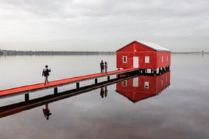 Perth, Australia Visitors take pictures of the Crawley Edge Boatshed on the Swan river, which has been covered in red to celebrate the arrival of Manchester United Football Club, in Australia as part of a pre-season tour
