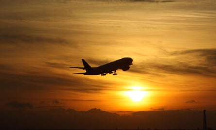 A plane taking off from Heathrow at sunset