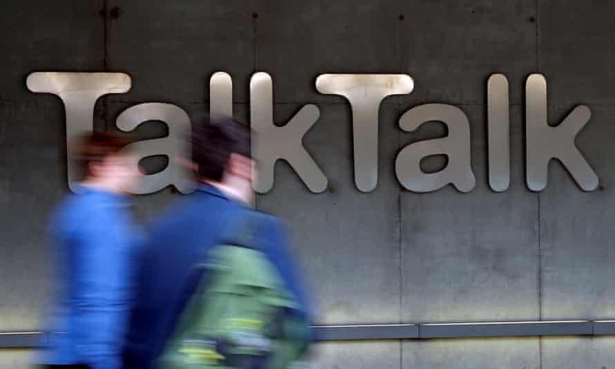 People walk past a company logo outside a TalkTalk building in London