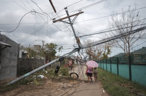 Residents pass by electrical posts toppled by Typhoon Goni in Malilipot, Philippines
