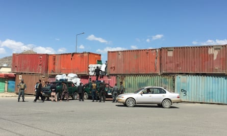 Afghan police use shipping containers to block the road.