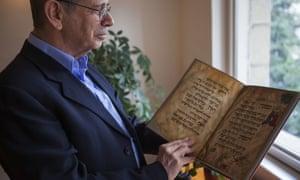 Eli Barzilai holds a copy of Haggadah