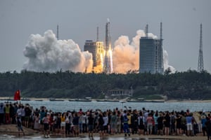People watch a Long March 5B rocket, carrying China's Tianhe space station core module, as it lifts off from the Wenchang space launch centre in Hainan province in April