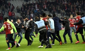 Stewards protect the players from fans at the Stade Pierre-Mauroy.