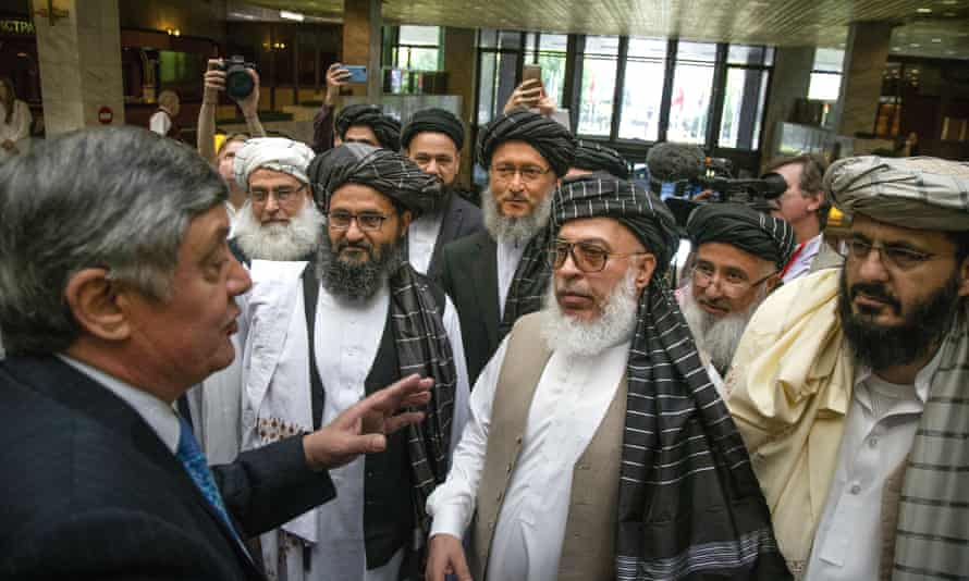 Russia's presidential envoy to Afghanistan, Zamir Kabulov (left), speaks to Taliban representatives including their leader, Abdul Ghani Baradar (third left), in 2019