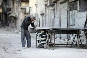 A man and boy mend steel doors in the neighbourhood of al-Shaar