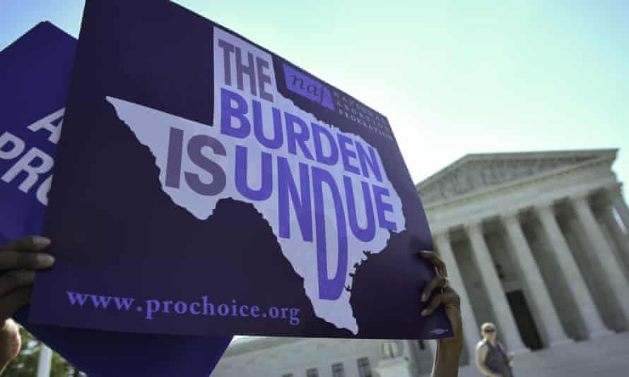 An abortion rights activist holds placards outside of the US supreme court last year. The Texas state representative Jessica Farrar has filed a bill parodying anti-abortion measures.