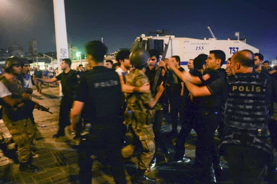 Turkish soldiers, arrested by civilians, are handed to police officers in Taksim Square in Istanbul.