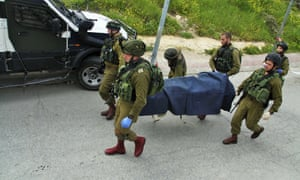 Israeli soldiers carry the body of a Palestinian in the West Bank city of Hebron last week.