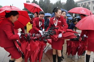 Attendants collect umbrellas after accompanying delegates to the Great Hall