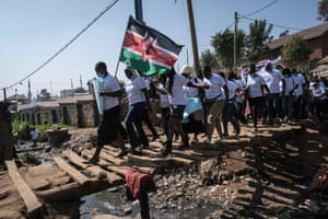 Kenya Human rights defenders from 26 community-based organisations march under the national flag for International Women's Day in Kibera, Nairobi.