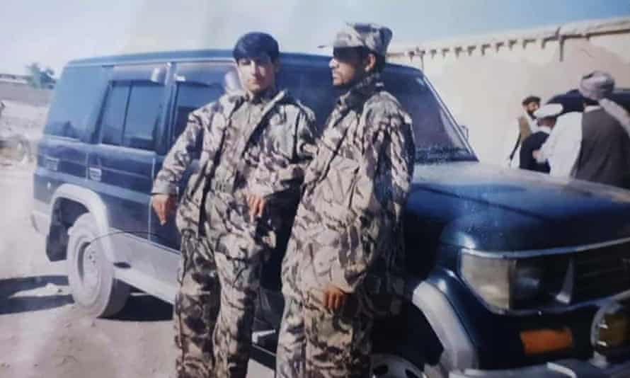 Afghan refugee FGS20, left, with a fellow guard, working for a provincial intelligence chief in Afghanistan. The other guard pictured here has since been killed by the Taliban.