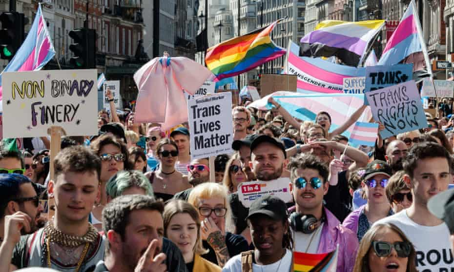 Attendees of Trans Pride march holding signs reading: 'Non-binary finery', 'Trans lives matter' and 'Trans rights now'