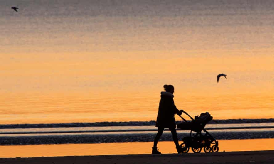 Mother with baby in a buggy walking down a beach on Portobello beach, Edinburgh