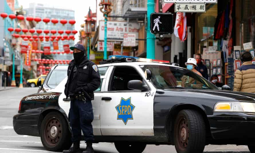 A San Francisco police officer stands guard on Grant Avenue in Chinatown. Police stepped up patrols in Asian neighborhoods in the wake of a series of shootings in Atlanta.