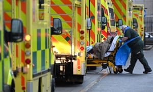 A paramedic is seen by a line of ambulances outside the Royal London hospital in east London