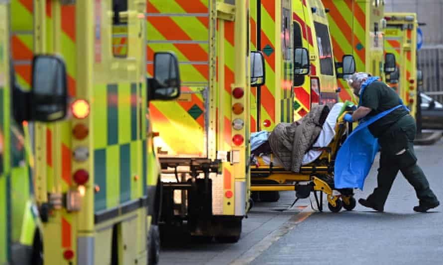 A paramedic is seen by a line of ambulances outside the Royal London Hospital.