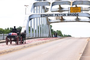 A horse-drawn carriage carrying the body of John Lewis crosses the Edmund Pettus Bridge in Selma, Alabama, on 26 July