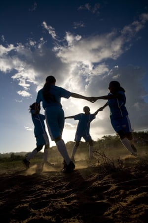 Girls from a female football team in Capa, Brazil dance in a circle