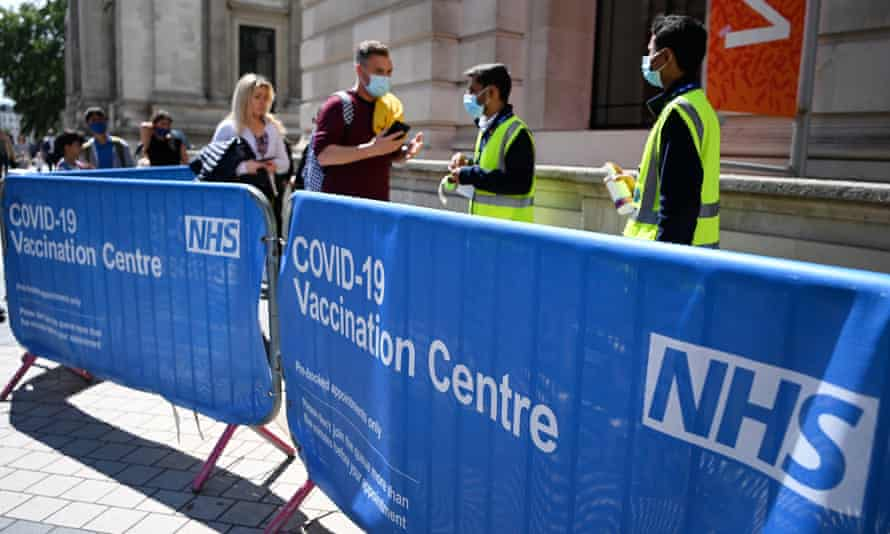 Young people lineup to get vaccinated in London on Friday.