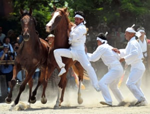 Fukushima, Japan Men wearing white, called Okobito, try to capture horses during the Nomagake ritual at the end of the Soma Nomaoi festival