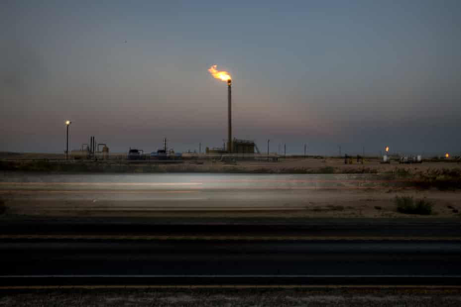 A gas flare is seen in a field at dusk near Mentone, Texas, in August 2019.