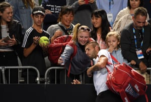 Dan Evans takes a selfie with a fan as he heads off court after a famous victory.