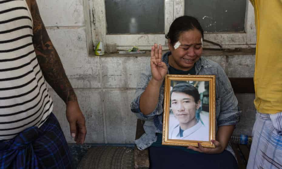 Une femme qui pleure salue ses trois doigts alors qu'elle tient une photo de son parent qui a été abattu par les forces de sécurité la veille
