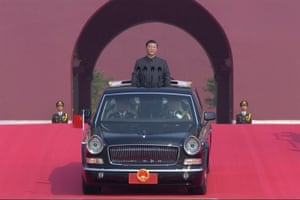 The Chinese leader, Xi Jinping, rides an open-top limousine during the parade