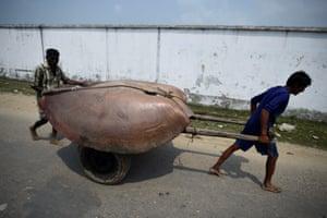 Bangladeshi men wheel a manta ray past Nazirartek fish-drying yard