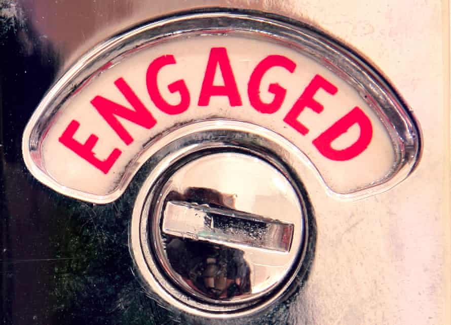 A traditional 'Engaged' toilet door lock sign with the word engage, finished in chrome on a pine door.