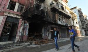 Lebanese boys walk past a burned building in Tripoli's Bab al-Tabbaneh area in October 2014.