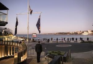 A small group gathers for an Anzac Day dawn service outside North Bondi RSL Club at Bondi beach.