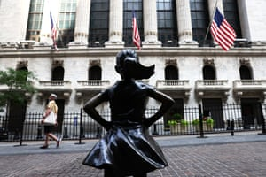 """A pedestrian walks near the """"Fearless Girl"""" statue in front of the New York Stock Exchange (NYSE) at Wall Street on July 23, 2020 in New York City."""