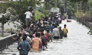 People wade through a water-logged road in Chennai, capital of southern Indian state Tamil Nadu