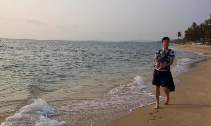 Tom Ravenscroft with his baby on a beach in Vietnam.