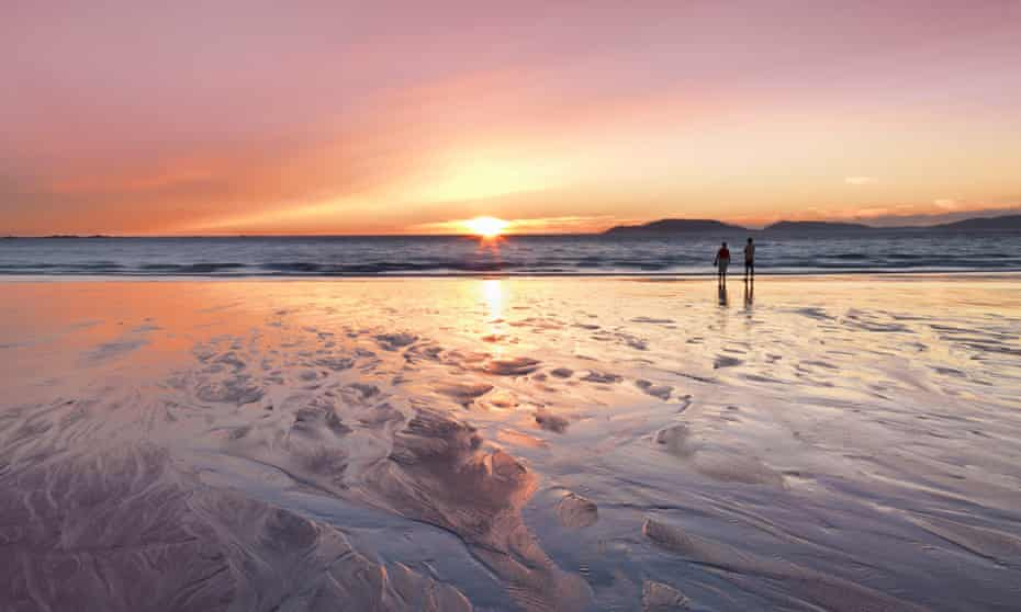 Couple  watching sunset at Carnota beach.