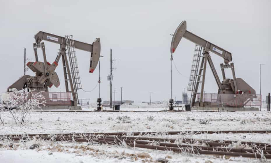 Pump jacks operate in the snow in the Permian Basin in Midland, Texas.